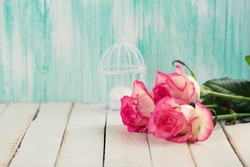 Background with fresh flowers. Roses on white wooden table. Selective focus is on right rose. Toned image.