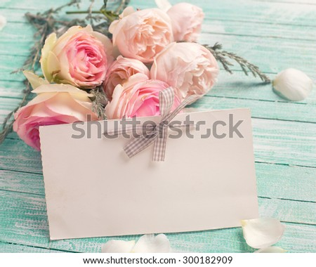 Background with fresh roses flowers and empty tag for your text on turquoise painted wooden background. Selective focus in on tag. Toned image.