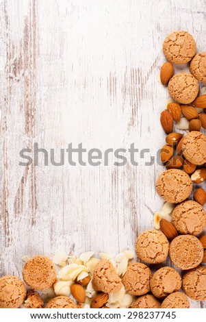 Background with italian almond cookie amaretti and almonds on white vintage table, food concept with copy space, top view.