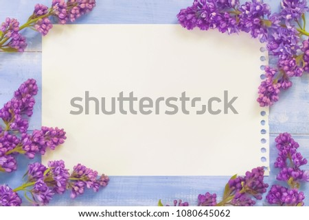 Branch of purple lilac spring flowers on vintage blue wooden