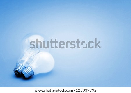 Background with lit lightbulb. Isolated on blue