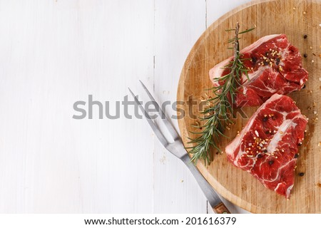 Background with red meat and rosemary over white wooden table. Top view #201616379