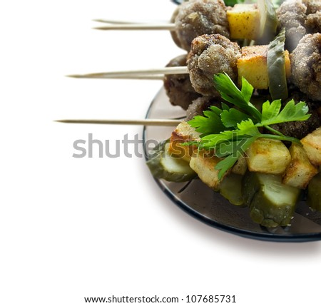 Background with roast meatballs on skewers with pickles and fried potatoes