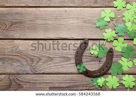 Background with rusty horseshoe and paper clover leaves on the old wooden boards. St.Patrick's day holiday symbol. Lucky charms.Space for text.