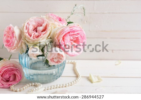 Background with sweet pink roses flowers  in blue vase on white painted wooden background. Selective focus. Place for text. Toned image.