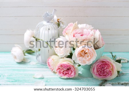 Background with sweet pink roses in vase and candle  on turquoise painted wooden planks against white wall. Shabby chic.  Selective focus.