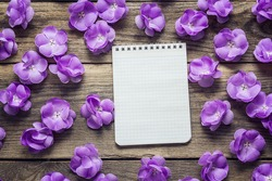 Background with violet flowers and empty notebook for text on old wooden  boards. Place for text. Top view with copy space