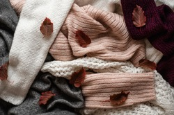 Background with warm sweaters. Pile of knitted clothes with autumn leaves, warm background, knitwear, space for text, Autumn winter concept. Copy Space.