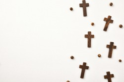Background with wooden crosses and round beads arranged to the right on wooden table. Horizontal composition.
