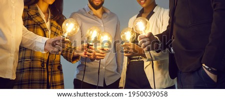 Background with young multiethnic business team holding glowing vintage Edison lightbulbs. Multiracial men and women join shining electric light bulbs as metaphor for teamwork and sharing creative