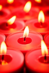 Backgrounds and textures: close-up shot of burning red candles, selective focus, holiday or celebration background