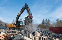 Backhoe clears rubble from building demolition