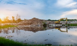 Backhoe is lifting refuse at waste separation plant, Mountain large garbage pile and pollution, Pile of stink and toxic residue