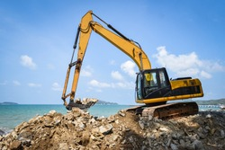 backhoe loader digger / Excavator working construction site on the beach sea ocean and blue sky background