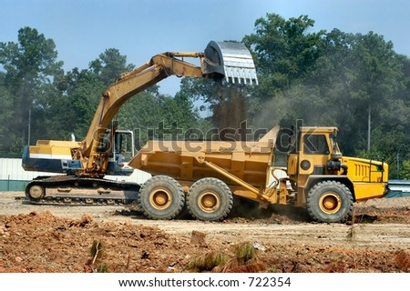 Backhoe pours dirt into a waiting dump truck - stock photo