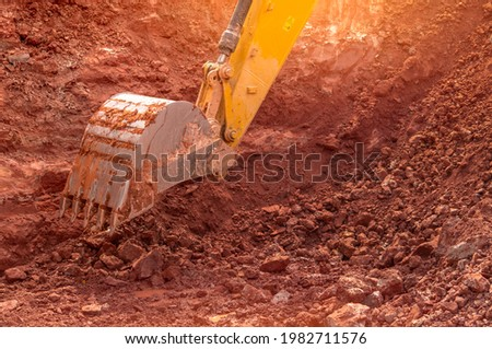 Backhoe working by digging soil at construction site. Bucket of backhoe digging soil. Crawler excavator digging on dirt. Closeup backhoe bucket of yellow backhoe. Earthmoving. Trenching machine. Photo stock ©