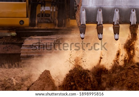 Backhoe working by digging soil at construction site. Bucket teeth of backhoe digging soil. Crawler excavator digging on soil. Excavating machine. Earth moving machine. Excavation vehicle.