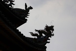 Backlight silhouette of a black fantasy dragon sculpture with religious architectural ornaments and asian decorations on traditional roof of Bangka Mengjia Longshan Temple in Wanhua, Taipei, Taiwan.