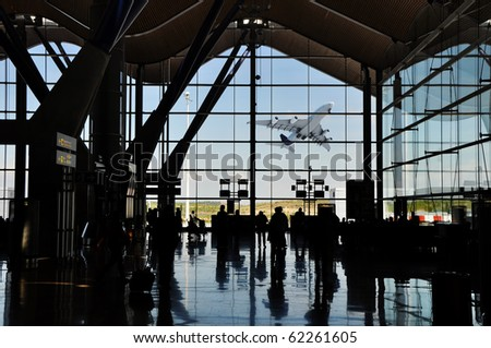 Backlight silhouette of poeple in an airport terminal with an espectacular plane takeoff ouside