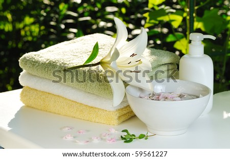 backlighting with sun white lily on stack of towels against green summer background