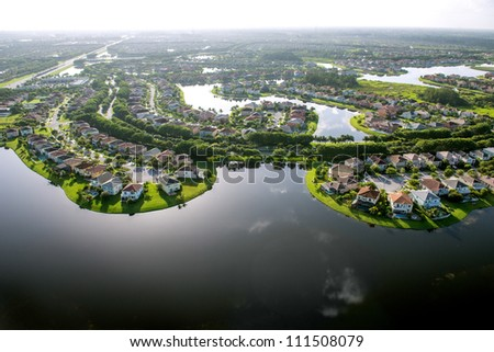backlit aerial view of luxury florida suburban residential community around lakes