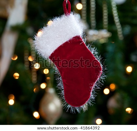 Backlit fur stocking in front of out of focus christmas tree and lights