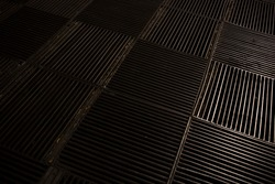 Backlit grid of thin parallel metal cover protection for opening on pavement level prevents people and objects from falling into pit. Dark square metallic manhole cover background on street surface