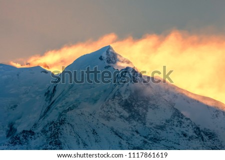 Backlit image at the sunrise on Mont Blanc - the highest mountain peak in Europe. In the first plan you can see L'aiguille de Bionnassay.
