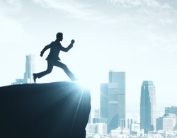 Backlit image of man silhouette jumping off cliff on city background. Achievement concept