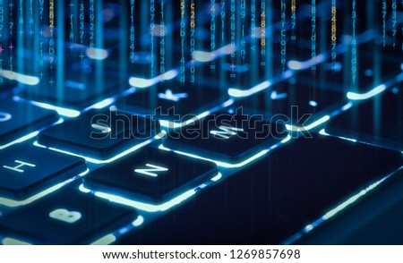 backlit keyboard  with piece of code in background