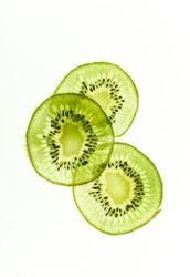 Backlit kiwi fruit slices on white background