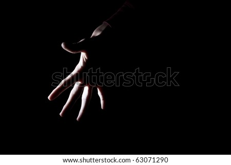 backlit outline of spooky human hand isolated on black for text