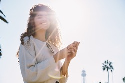 Backlit portrait of funny female tourist 20s posing during travel vacations, happy millennial blogger holding modern smartphone device in hands and smiling at camera enjoying getaway journey