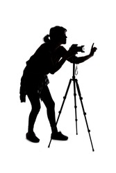 Backlit silhouette of a female photographer hiking and isolated on a white background for composites.  She is holding a camera and posing as a journalist or a hobbyist