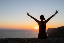 Backlit silhouette of a woman watching the sunrise over the sea making victory sign