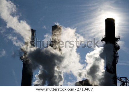 Backlit silhouettes of smoke stacks of a coal-burning power plant