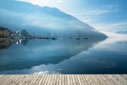 Backlit view of boats anchored at the Traunsee in Gmunden, OÖ, Austria with the Grünberg rising in the background