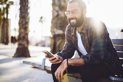 Backlit view of cheerful hipster guy in sunglasses holding takeaway cup and cellular gadget in hands and smiling, happy Middle Eastern male blogger with mobile phone resting at bench in city