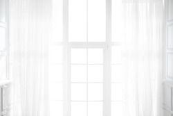 Backlit window with white curtains in empty room