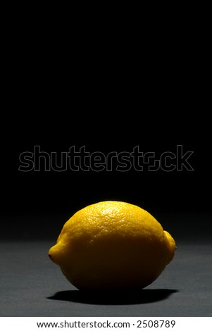 Backlit yellow lemon over black