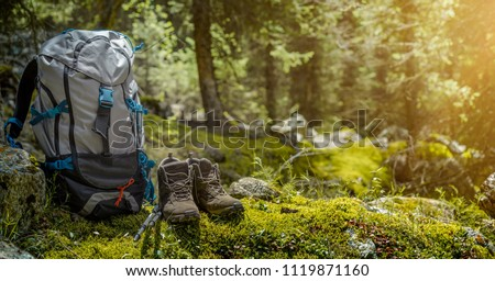 Backpack and hiking boots in forest #1119871160