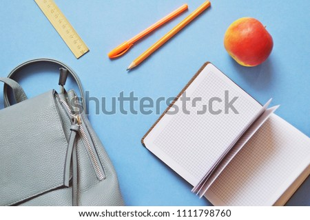 Backpack, exercise book, orange pen and pencil, red apple on a blue table. Back to school concept. Flat lay photo study, training. School education photography