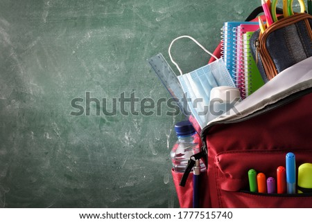 Backpack full of school supplies with mask and gel protection for covid-19 with green blackboard with blank space for writing front view