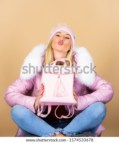 Backpack is all you need. Little backpack and knitted hat. Total pastel outfit. Tender combination. Matching accessories. Fashion accessory. Girl adorable model showing her fancy leather backpack.