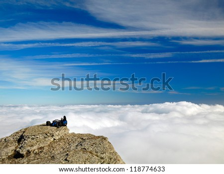 Backpack on the rock over clouds and sky background