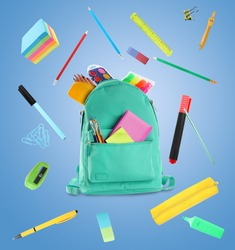 Backpack surrounded by flying school stationery on light blue background