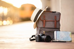 Backpack travel with hat, camera, map, earphone and smart phone on the ground of train station at sunset background train. travel and backpack concept.