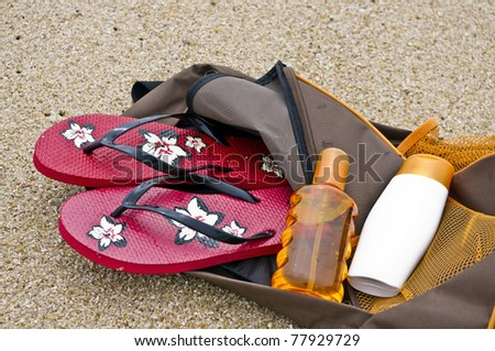 Backpack with beach items like flip-flops, sunscreen all this on the sand - stock photo
