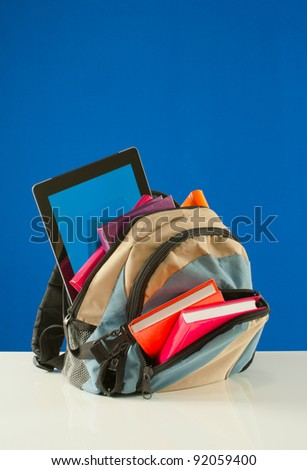 Backpack with colorful books and tablet PC on blue background
