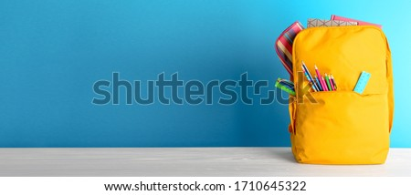 Backpack with different colorful stationery on table. Banner design